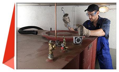 Tankschutzmonteur arbeitet an einem Heizöltank